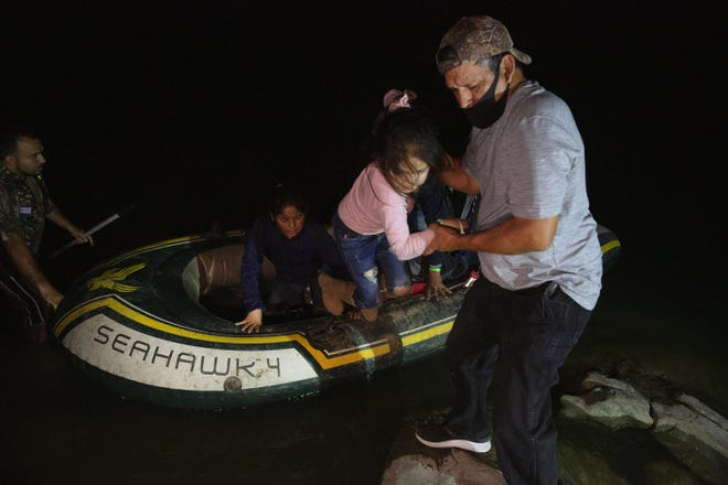 A little girl is helped off an inflatable raft by a church volunteer after being smuggled across the Rio Grande in Roma on March 30. [AP PHOTO/DARIO LOPEZ-MILLS/FILE]
