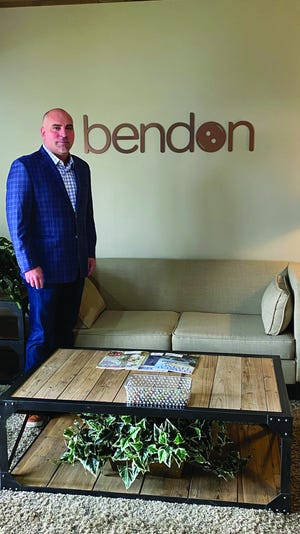 Ben Ferguson, president and Chief Executive Officer of Bendon Publishing, stands besides the Bendon logo.