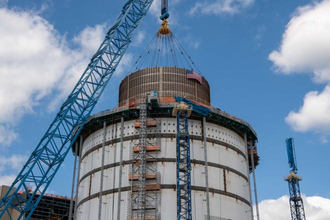 A crane lowers a 360-ton water tank atop Plant Vogtle's Unit 4, in this photo provided by Georgia Power Co.
