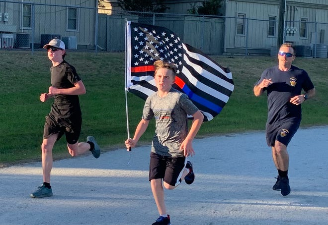 Zechariah Cartledge, 12, of Orlando, leads a one-mile run at the Family YMCA on Wheeler Road to honor the area's fallen heroes as part of his nonprofit Running 4 Heroes. Joining him on the track are Richmond County Sheriff's Office family member Kamden Runyon, left, and Augusta Fire Lt. Trey Cashwell.