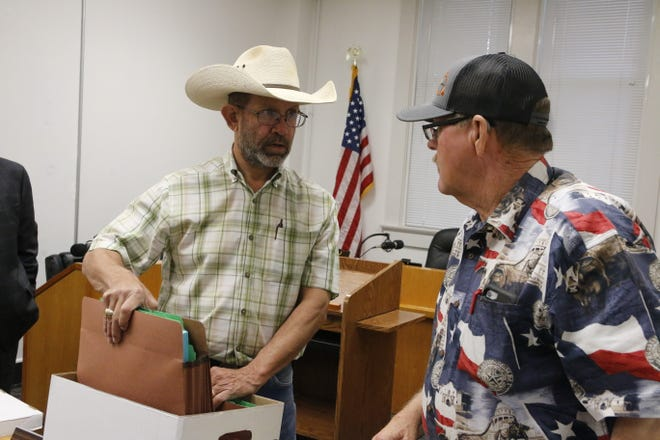 TLOW member Steven Wilson (center) stands holds files of signatures for a petition as he speaks with Precinct 4 commissioner Larry Traweek after Monday morning's meeting of the Brown County Commissioners Court.