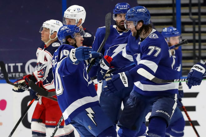 The Tampa Bay Lightning's Alex Barre-Boulet (60) celebrates his first NHL goal with Victor Hedman (77) and Alex Killorn (17) early in the third period of the Blue Jackets' 4-3 overtime loss Sunday at Amalie Arena in Tampa, Fla.