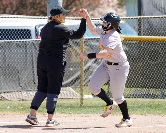 Adrian College's Lauren McCulligh high-fives head coach Ashley Skelly after hitting a home run during Sunday's game against Anderson.