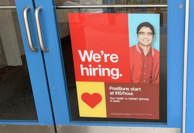 A hiring sign can be seen on one of the entrance doors to the Target store on Dunlawton Avenue in Port Orange on April 10, 2021.