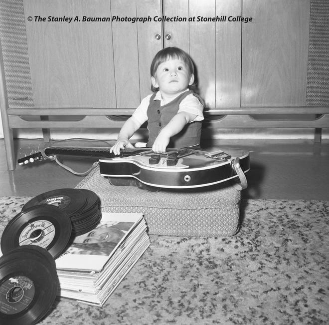 "Brockton's youngest Beatles fan: Robert ""Bobby"" C. Longe, the 14-month-old son of Claudette M. Longe, of 20 South St. in Brockton, exhibited his Beatles talent with a guitar, complete with a Beatles-like hairdo, on April 27, 1964."