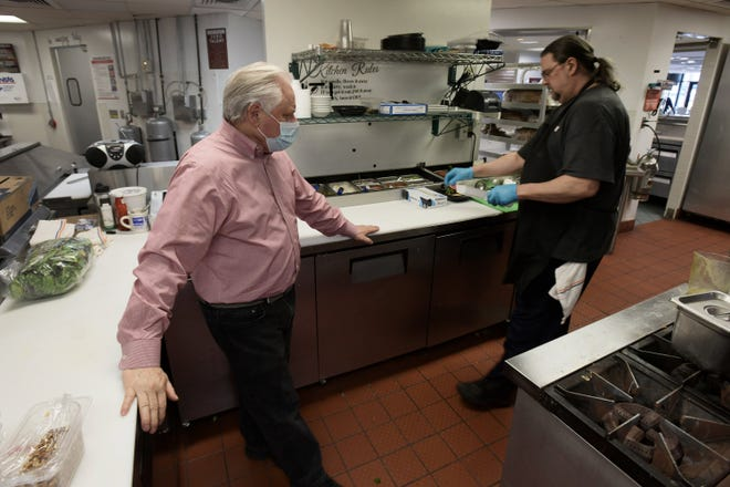 Kelly Harris, co-owner of the Village Bread Cafe, checks the kitchen with chef Kent Beaumont as the lunchtime rush winds down at the company's Riverplace Tower location.