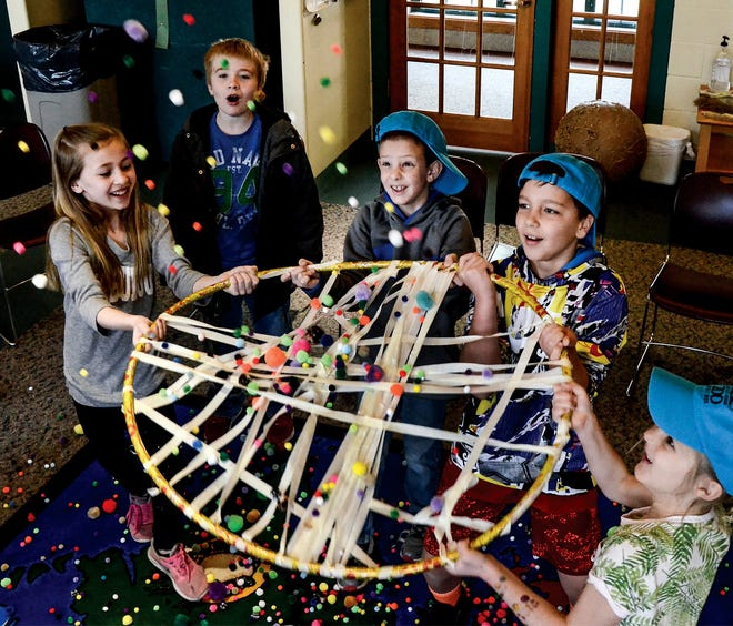 """A group of Lee Richardson Zoo Edventure Camp participants try to catch """"flies"""" (pom pons) with a trap they made using a Hoola Hoop and masking tape during a past camps activity on carnivorous plants. LRZ has announced the dates for the return of its Edventure camps for the summer."""