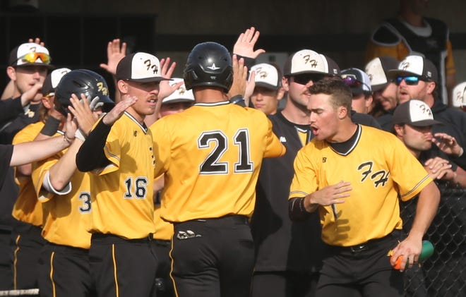 Grant Schmidt is greeted by his Tiger teammates after scoring a run on Saturday against Washburn at Larks Park.
