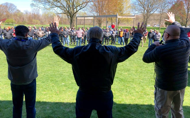 Rev. Dave Lantz, left, Rev. Greg TenBrink, center, and Rev. Gregory J. Kett pray over the group of motorcyclists gathered for the annual Blessing of the Bikes Sunday, April 25, 2021, at Beechwood Church.