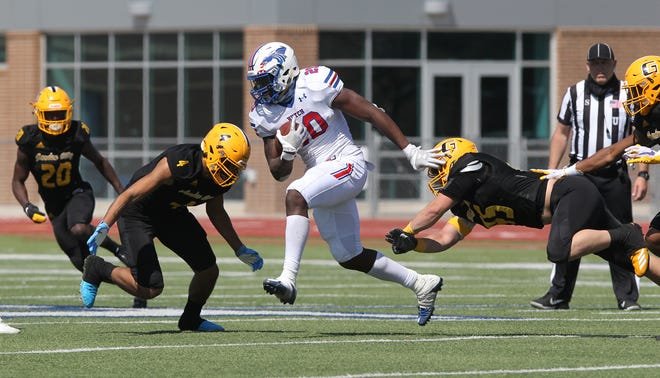 Hutchinson's Tye Edwards (20) runs past Garden City's Mailei Wembley (4) and Christian Fuhrman (45) during their game earlier in the spring at Gowans Stadium. Hutchinson defeated Garden City 23-7.