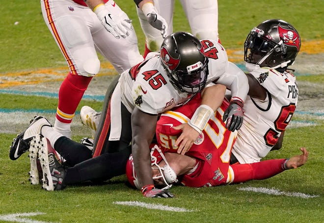 FILE - Kansas City Chiefs quarterback Patrick Mahomes (15) is sacked by Tampa Bay Buccaneers inside linebacker Devin White (45) and outside linebacker Jason Pierre-Paul (90) during the second half of NFL Super Bowl 55. The next opportunity to provide some help up front for quarterback Patrick Mahomes is the NFL draft.