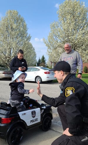 Monroe County Sheriff's Deputy Zachary Straub high-fives Easton Braden, 15 months, after the officer stopped in the Newport neighborhood and spent some time with the toddler. The toddler's grandparents are Wayne and Jennifer Braden.