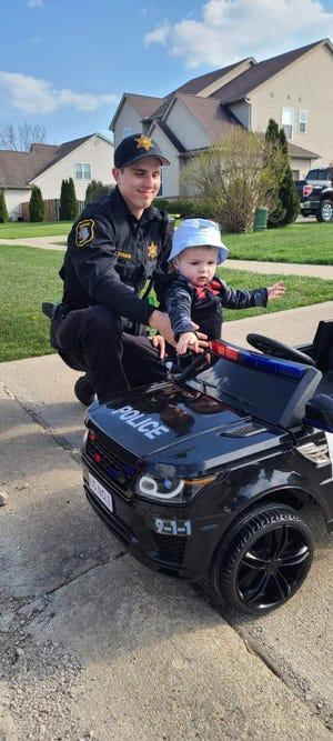 Deputy Zachary Straub helps Easton Braden, 15 months, into the toddler's police car.