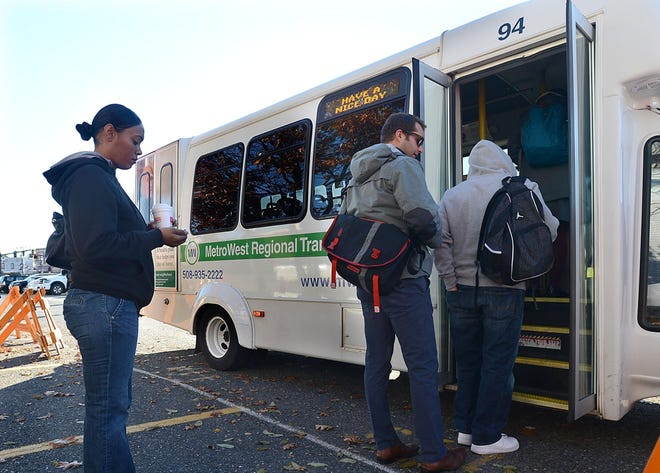 """Morning commuters board a MetroWest Regional Transit Authority bus bound for Marlborough at the MWRTA """"banana lot"""" in downtown Framingham."""