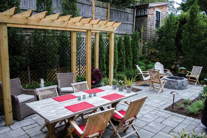 Paving stones both define and unify the separate areas. Landscape architect Katie Adams softened the existing retaining wall with hornbeams and arborvitaes, and installed a pergola for additional privacy.