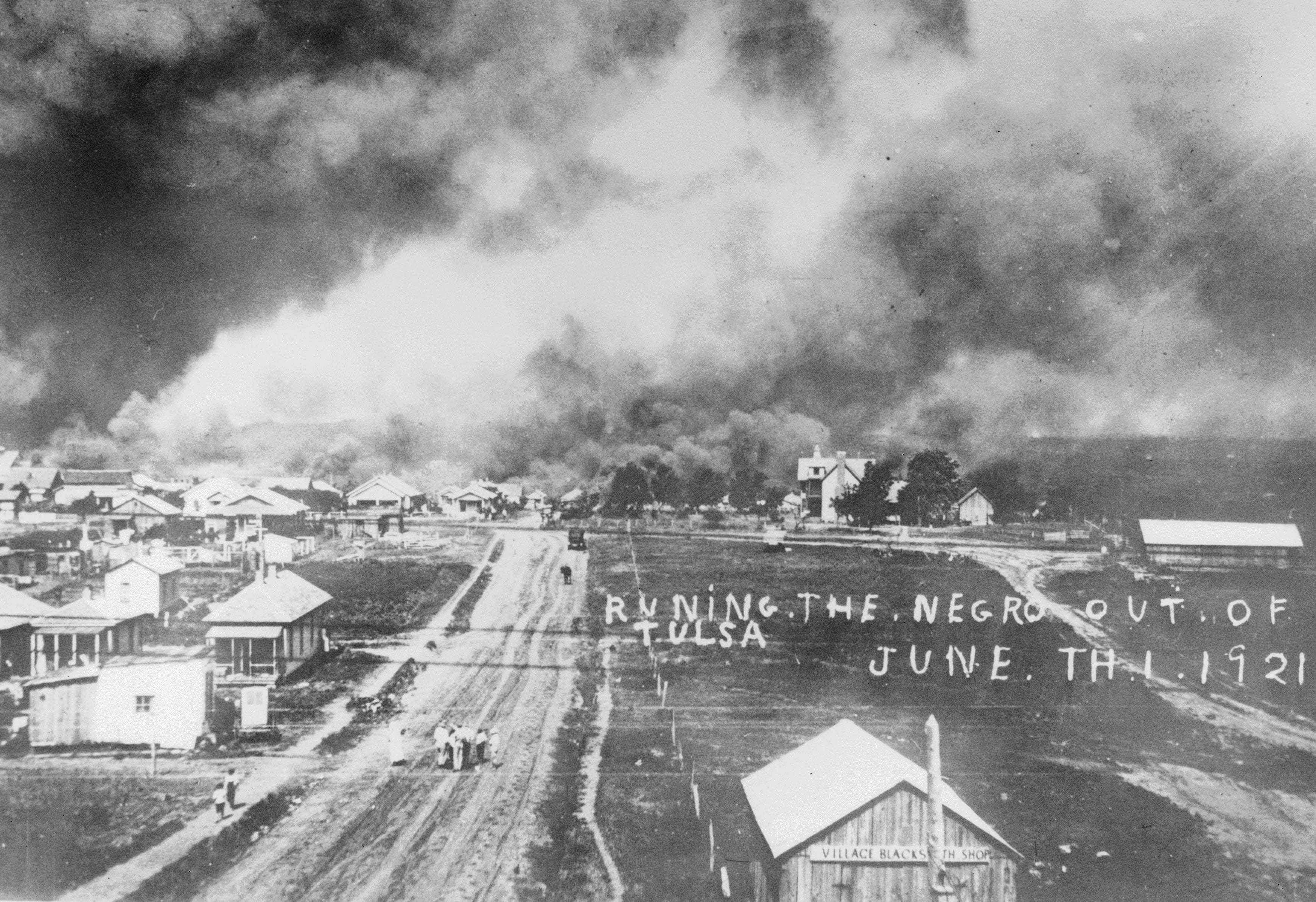 """Picture postcards were printed proclaiming """"running the negro out of Tulsa"""" against a backdrop of the smoldering ruins of people's homes."""