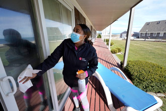 Worker Jennifer Porter, of Hyannis, Mass., cleans windows, Tuesday, April 6, 2021, at Red Jacket Resorts, in Yarmouth, Mass. Hotels, restaurants and other businesses in tourist destinations are warning that hiring challenges during the coronavirus pandemic could force them to pare back operating hours or curtail services just as they're eyeing a bounce-back summer.