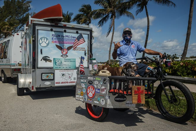 Jay Hamm, Jupiter, director of Paws For Compassion, prepares for his upcoming national bicycle tour to promote his local organization that provides pet therapy for the sick and infirm, with a press stop at Jupiter Beach Park in Jupiter, Fla., on Monday, April 26, 2021.