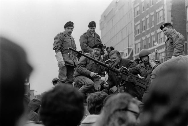 Cigar firmly clenched between his teeth, actor John Wayne arrives at Harvard Square in Cambridge, Massachusetts, aboard a tank on Jan. 15, 1974. Wayne, undeterred by criticism of his conservative views during the Vietnam War, was on hand to receive an award from the Harvard Lampoon humor magazine at the college.