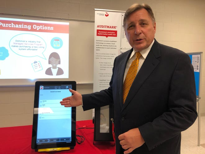 Mark Beckstrand, a regional sales manager for Dominion Voting Systems based in Denver, demonstrates a Dominion touchscreen voting device to Stark County officials on Sept. 12, 2018. The Stark County Board of Elections on Dec. 9, 2020 voted to purchase a different version of that system.