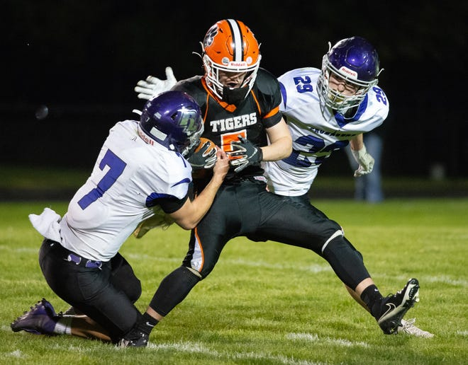 Rockford Lutheran's Joshua Oetting tries to strip the ball from Byron's Josiah Fetherston before he is tackled by Nolan Moore, 29, in the fourth quarter of their game in Byron on Friday, April 23, 2021. Lutheran won 6-0.