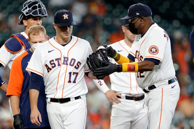 Houston Astros starting pitcher Jake Odorizzi (17) hands the ball off to manager Dusty Baker Jr. (12) as he leaves the mound with an injury on the second batter of the first inning of a baseball game agains the Los Angeles Angels on Saturday in Houston.