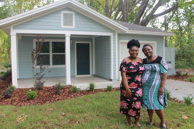 Virginia Lynn, right, stands next to her daughter Tammie Lynn, left, in front of their new home in East Gainesville that she purchased with the help of the Gainesville Neighborhood Housing and Development Corporation.