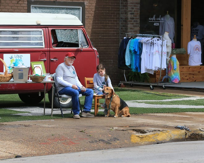 Travis McMillan and Quinn Smith, 9, are joined by a rescue dog, Merl, at the Almost Home Shelter booth in the annual Earth Day Festival, Saturday, April 24, in historic downtown Van Buren.