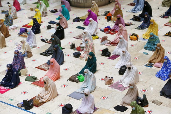 Muslim women wear face masks and practice social distancing at a Mosque in Jakarta