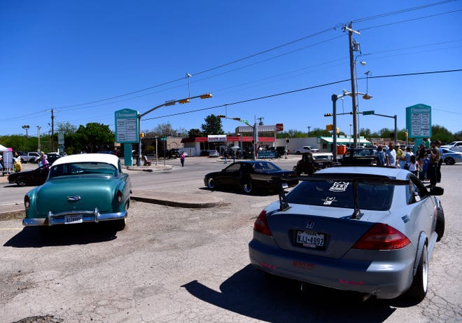 Cars cruise through the parking lot during the Elmwood West 70th Birthday Block Bash on Saturday.