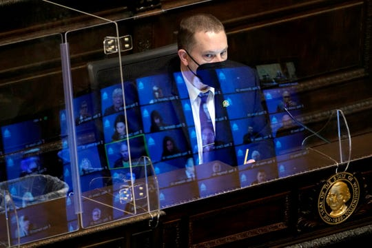 FILE - In this Wednesday, April 21, 2021 file photo, Gary Holt, who reads bills being considered in the Washington House, wears a mask as he sits behind a plexiglass shield with reflections of state representatives meeting remotely on it, at the Capitol in Olympia.