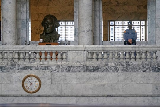 FILE - In this Jan. 13, 2021 file photo, a Washington State Patrol trooper stands near a bust of President George Washington in the Legislative Building at the Capitol in Olympia.