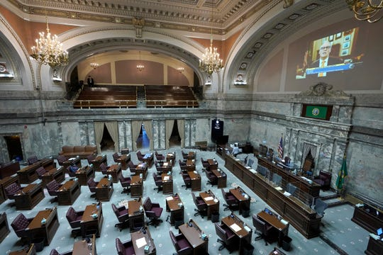 FILE - In this Jan. 13, 2021 file photo, a pre-recorded video of Washington Gov. Jay Inslee giving his inaugural address is played in the Senate chambers at the Capitol in Olympia.