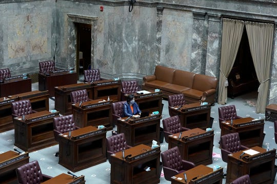 FILE - In this Jan. 13, 2021, file photo, Washington Sen. Emily Randall, D-Bremerton, works at her desk on the otherwise empty Senate floor, at the Capitol in Olympia during a joint session of the Washington Legislature being held remotely.
