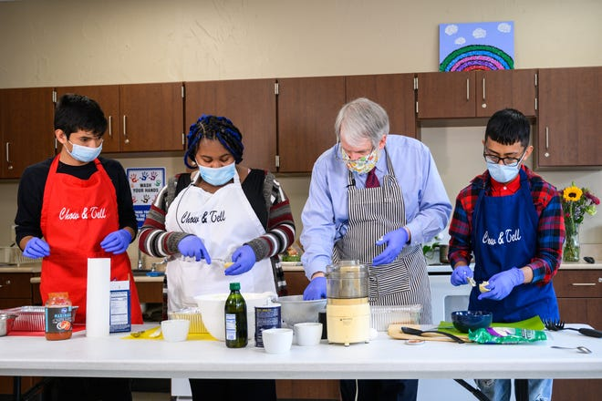 Students (from left to right) Josue Galvin, Nadya Meriweather and Josue Galvin cook with Ohio's superintendent of public instruction, Paolo DeMaria (center).