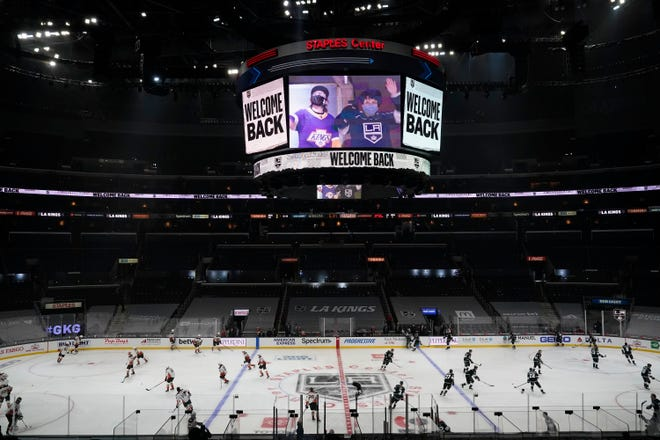 A sign welcomes back fans amid the COVID-19 pandemic as the Los Angeles Kings and Anaheim Ducks warm up before an NHL hockey game Tuesday, April 20, 2021, in Los Angeles.
