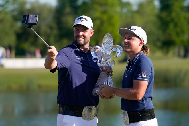 Marc Leishman, of Australia, left, and teammate Cameron Smith, of Australia, hold the trophy after winning the PGA Zurich Classic golf tournament at TPC Louisiana in Avondale, La., Sunday, April 25, 2021.