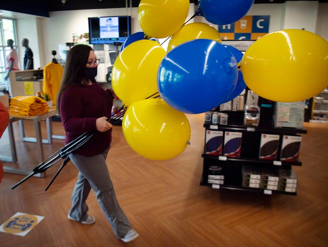 Lesley Cohron, assistant store manager, moves balloons back into storage after the ribbon-cutting ceremony for the HCC Barnes & Noble Bookstore at the Henderson Community College Monday afternoon, April 26, 2021.