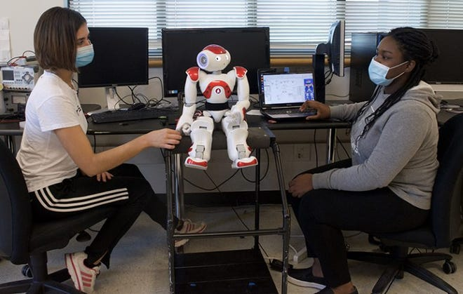 Undergraduates Janet Pulgares Soriano (left) and Rebecca Castelly (right) work on robotics research in the Machine Learning and Interaction laboratory at the University of Louisville.