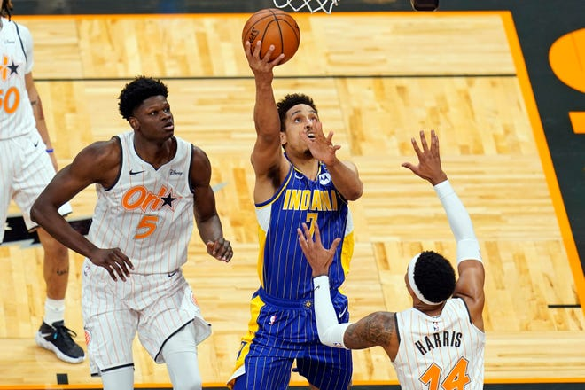 Indiana Pacers guard Malcolm Brogdon, center, goes up for a shot between Orlando Magic center Mo Bamba (5) and guard Gary Harris right, during the first half of an NBA basketball game, Sunday, April 25, 2021, in Orlando, Fla. (AP Photo/John Raoux)