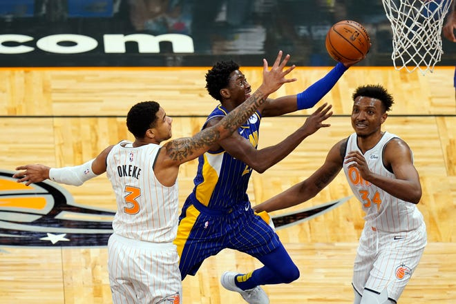 Indiana Pacers guard Caris LeVert, center, goes up for a shot between Orlando Magic forward Chuma Okeke (3) and center Wendell Carter Jr., right, during the first half of an NBA basketball game, Sunday, April 25, 2021, in Orlando, Fla. (AP Photo/John Raoux)