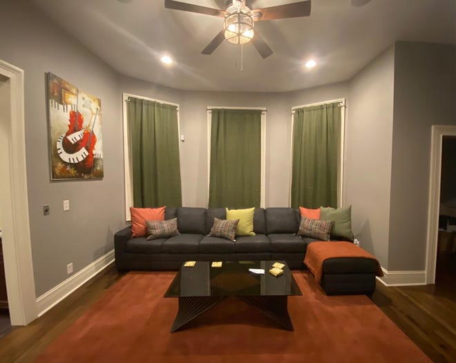 Part of the great room shows three windows and a sectional sofa that Jasmine M. Johnson had custom made.