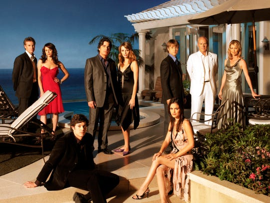 "The mid-2000s Fox series ""The O.C."" is the subject of a new rewatch podcast. The teen soap starred (left to right): Tate Donovan, Melinda Clarke, Peter Gallagher, Mischa Barton, Benjamin McKenzie, Alan Dale, Kelly Rowan, (seated) Adam Brody and Rachel Bilson."