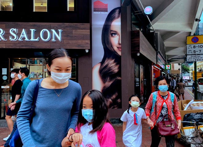 People wearing face masks to help protect against the spread of the coronavirus walk at a street in Hong Kong, Monday, April 26, 2021. Hong Kong and Singapore said Monday they would launch an air travel bubble in May, months after an initial arrangement that would allow tourists to fly between both cities without having to serve quarantine was postponed. Flights will begin from May 26.