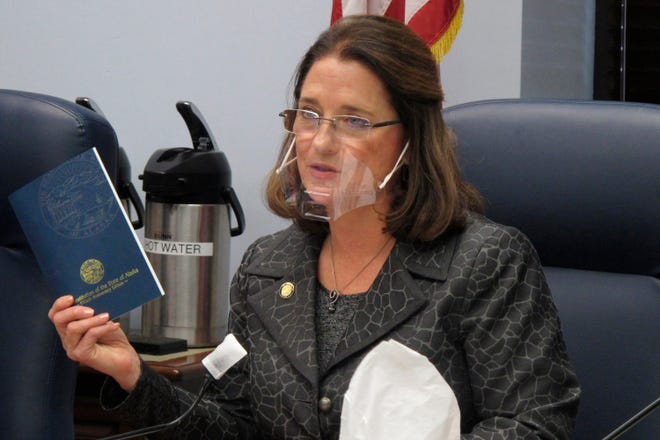 In this Jan. 27, 2021 file photo, Alaska state Sen. Lora Reinbold, an Eagle River Republican, holds a copy of the Alaska Constitution during a committee hearing in Juneau, Alaska. Alaska Airlines has banned the Alaska state senator for refusing to follow mask requirements. Last week Reinbold was recorded in Juneau International Airport arguing with Alaska Airlines staff about mask policies. A video posted to social media appears to show airline staff telling Reinbold her mask must cover her nose and mouth. Reinbold has been a vocal opponent to COVID-19 mitigation measures and has repeatedly objected to Alaska Airlines' mask policy, which was enacted before the federal government's mandate this year.