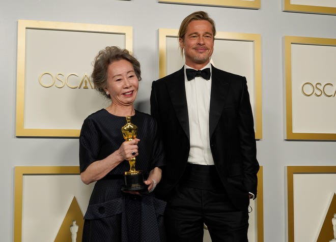 """""""Minari"""" star Yuh-jung Youn, left, and producer Brad Pitt pose for a picture backstage at the Oscars."""