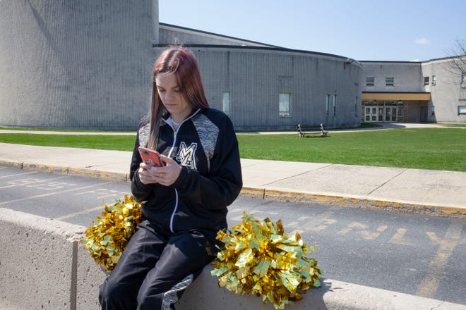 Brandi Levy wears her former cheerleading outfit as she looks at her mobile phone while sitting outside Mahanoy Area High School in Mahanoy City, Pa., on April 4, 2021. This photo was provided by the American Civil Liberties Union.