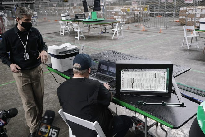 Doug Logan, left, owner of Florida-based consultancy Cyber Ninjas, talks about overseeing a 2020 election ballot audit ordered by the Republican-led Arizona Senate at the Arizona Veterans Memorial Coliseum, as a Cyber Ninjas IT technician demonstrates a ballot scan during a news conference on April 22 in Phoenix. The equipment used in the November election won by President Joe Biden and the 2.1 million ballots cast in Maricopa County were moved to the site Thursday so Republicans in the state Senate who have expressed uncertainty that Biden's victory was legitimate can recount them and audit the results.