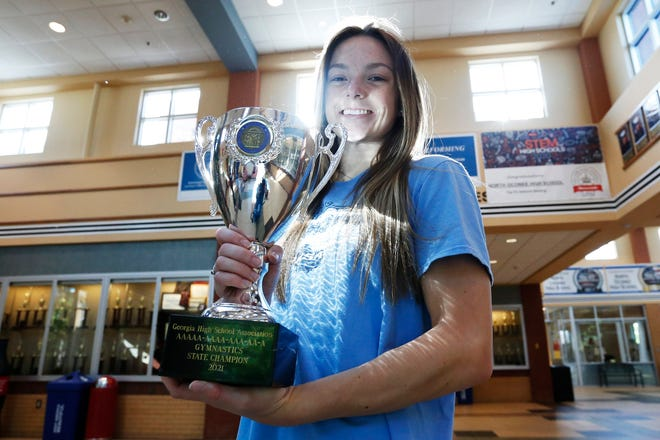 North Oconee's Maylen Pulliam poses for a photo with the 2021 State Championship gymnastics trophy after helping lead the Titans to Saturday's state title. (Photo/Joshua L. Jones, Athens Banner-Herald)