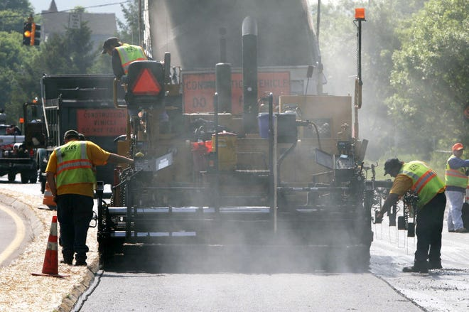 A crew works on resurfacing a road in this file photo.